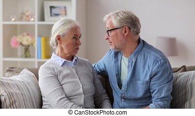 sad senior couple hugging at home - relationships, old age...