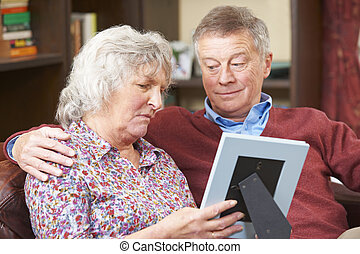 Sad Senior Couple Looking At Photograph In Frame Together