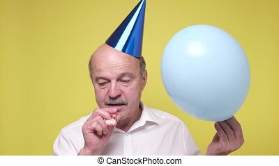 Sad senior father wearing cone hat and shirt feeling tired on his birthday party. Studoi shot on yellow wall.