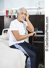 Sad Senior Man Holding Cane At Rehab Center - Portrait of...