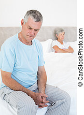 Sad senior man on bed with wife in background