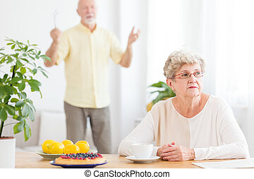 Sad senior woman arguing with her husband