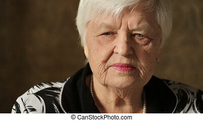 Sad Senior Woman at the room - Lonely old woman sitting on a...