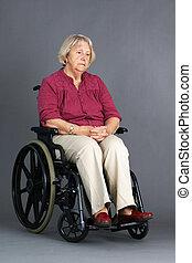 Sad senior woman in wheelchair