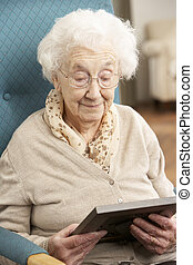 Sad Senior Woman Looking At Photograph In Frame