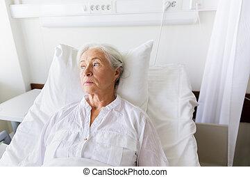 sad senior woman lying on bed at hospital ward - medicine,...