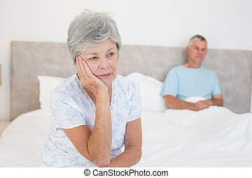 Sad senior woman on bed with husban - Sad senior woman...