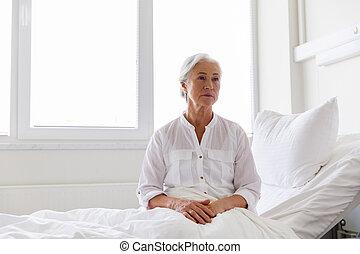 sad senior woman sitting on bed at hospital ward - medicine,...