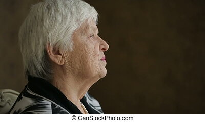 Sad Senior Woman - Lonely old woman sitting on a chair in a...