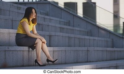 Sad stressed asian business lady sitting on stairs