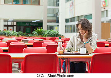 Sad student in the cafeteria with food tray