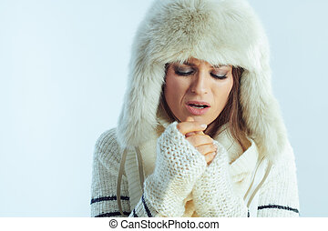 sad stylish woman warming hands with breathing
