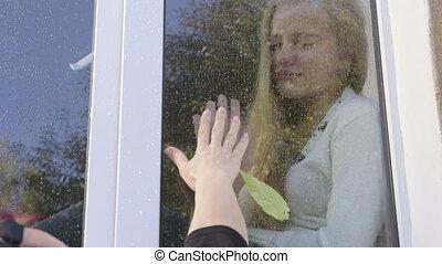 Sad tearful teenage girl says goodbye to her mother through window pane