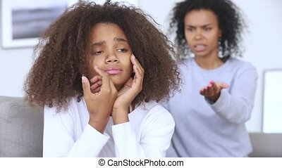 Sad teen african girl upset by strict mum scolding daughter...
