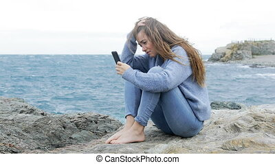 Sad teen complaining after reading phone message - Sad teen...