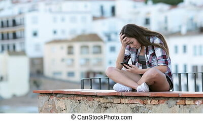 Sad teen crying after reading text on a phone - Sad teenage...