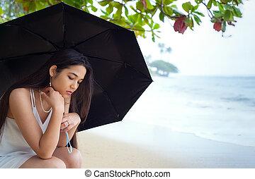 Sad teen girl on holding umbrella on rainy Hawaiian beach