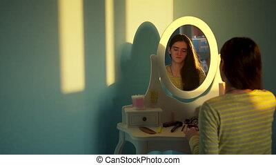 Sad teen girl sitting in front of a mirror and looking at herself