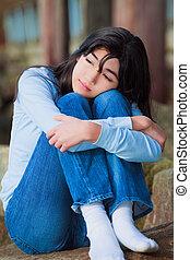 Sad teen girl sitting on rocks along lake shore, lonely expression
