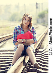 Sad teen girl with heart sitting at railway.