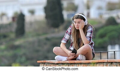 Sad teen listening to music on vacation sitting on a ledge...
