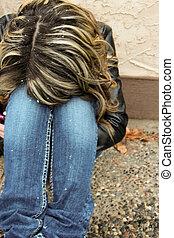 Sad teen with head on knees