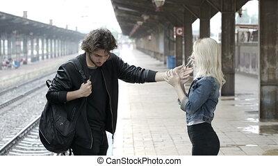 Sad teenage couple saying goodbye on train station platform