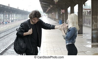 Sad teenage couple saying goodbye on train station platform