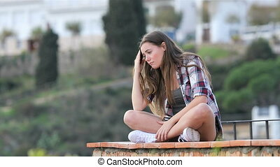 Sad teenage girl complaining sitting on a ledge