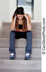 Sad teenager girl sitting on the stairs