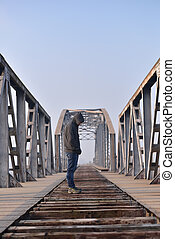 Sad teenager in depression sitting on the bridge at the sunset. Concept teenage problems. Selective focus