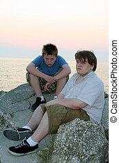 Sad Teens 3 - Two sad teenage boys sitting on rocks by the...