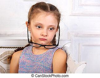 Sad thinking calm kid girl in eyeglasses looking. Closeup studio portrait