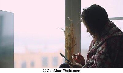 Sad thoughtful woman in plaid sitting on a window sill...