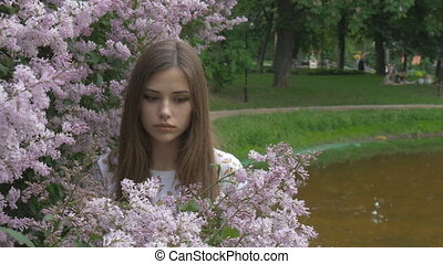 The young girl is enjoying the scent of lilac. Breathes the...