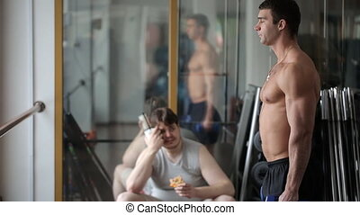 Sad tired fat man watches his athletic fellow training arm muscles with dumbbells