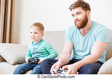 Sad unhappy dad and son playing computer games