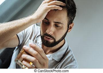 Sad unhappy man looking at his glass