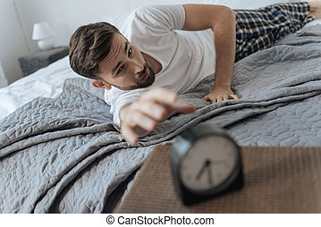 Sad unhappy man trying to reach the alarm clock