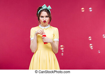 Sad unhappy young woman standing and blowing soap bubbles