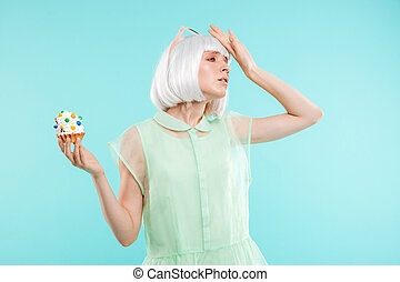 Sad upset blonde young woman refusing of sweet cupcake