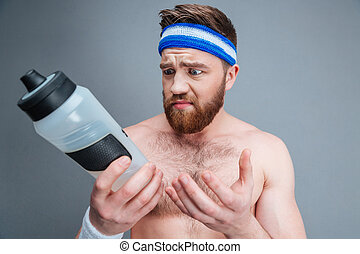 Sad upset young sportsman with empty bottle for water