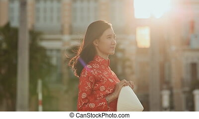Sad Vietnamese woman waiting for a meeting in the evening at sunset