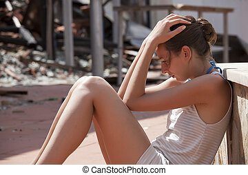 sad woman sitting in front of burned out house and holds her head with both hands