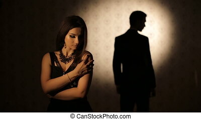 Sad woman and silhouette of a man