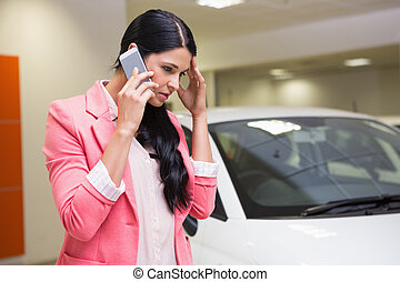 Sad woman calling someone with her mobile phone at new car ...