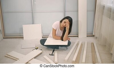 Sad woman can't to assemble furniture