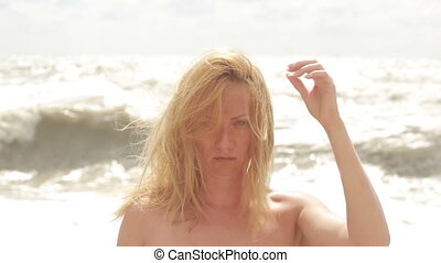 Sad woman crying during storm on the beach. hair fluttering in the wind