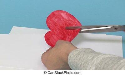 Sad woman cuts heart shape with scissors