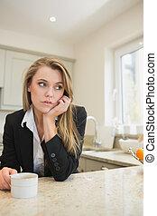 Sad woman drinking hot beverage